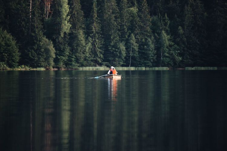 People rowing on lake against trees
