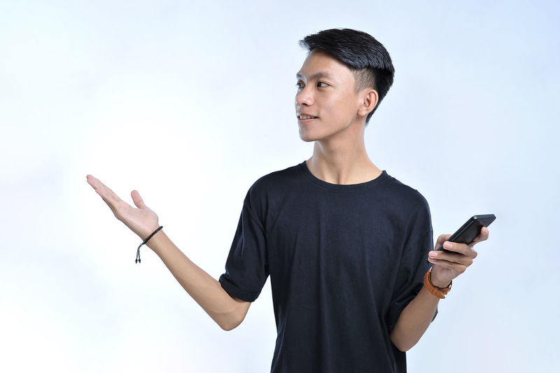 Young man using mobile phone against clear sky