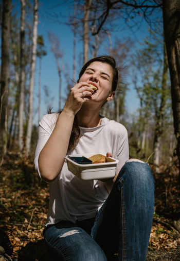 Young woman eating food while sitting in forest