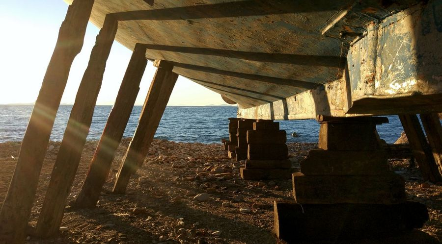 under the belly Hull Beach Below Built Structure Day Different Perspective Horizon Over Water Keel Nature Nautical Theme No People Outdoors Sea Shipyard Sky Under The Boat Underneath Water Wood - Material