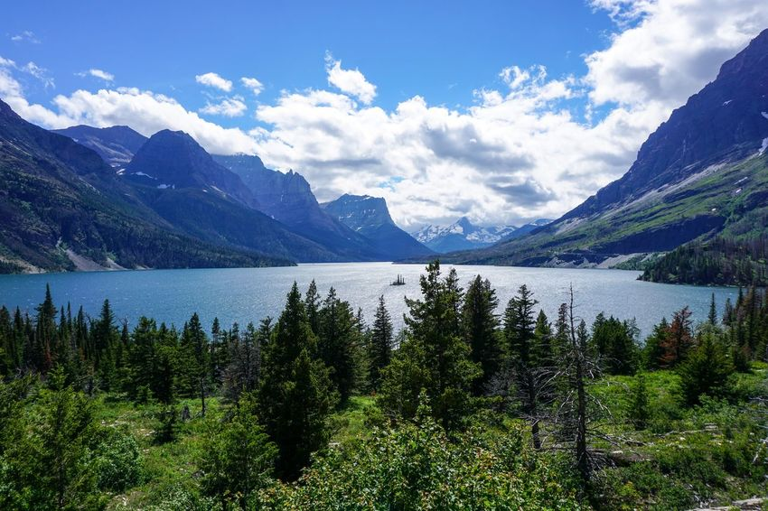 Beauty In Nature Cloud - Sky Environment Glacier National Park Growth Height High Lake Landscape Mountain Mountain Range Nature No People Outdoors Plant Range Reflection Scenery Scenics - Nature Sky Tranquil Scene Tranquility Tree Water Wilderness