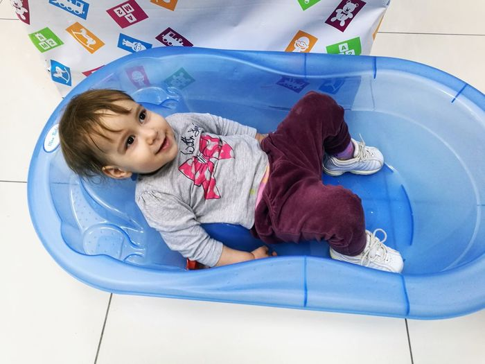 High Angle View Of Cute Boy Lying In Tub On Tiled Floor