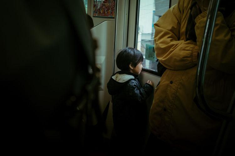 Rear view of boy standing by train window