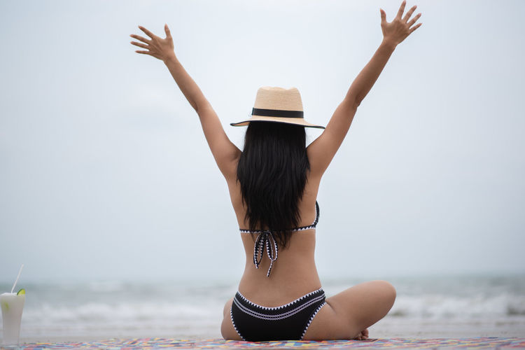 Sea Water Leisure Activity Young Women One Person Human Arm Clothing Real People Lifestyles Rear View Young Adult Women Adult Long Hair Sky Arms Raised Beach Hairstyle Vacations Hair Horizon Over Water Outdoors Sun Hat Freedom Beautiful Woman