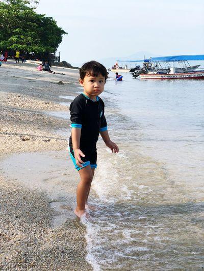 Portrait Of Boy Standing On Beach Against Sky
