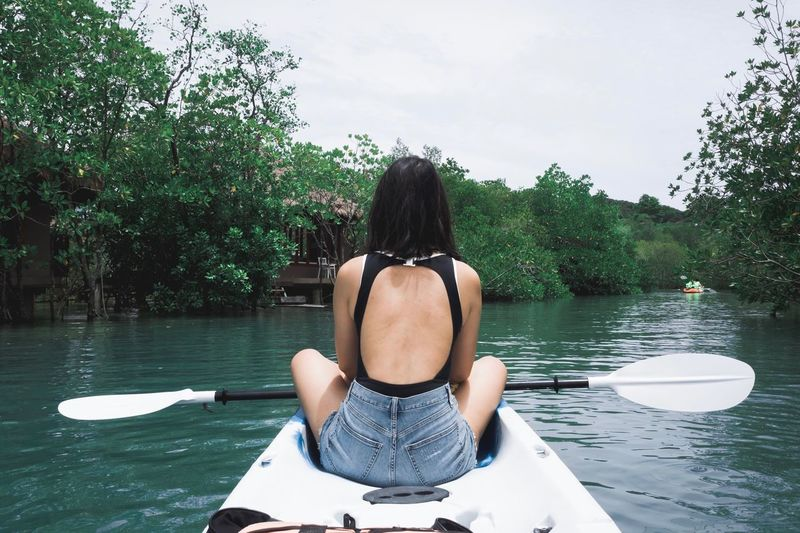 Rear View Of Woman Sitting In Boat On Lake