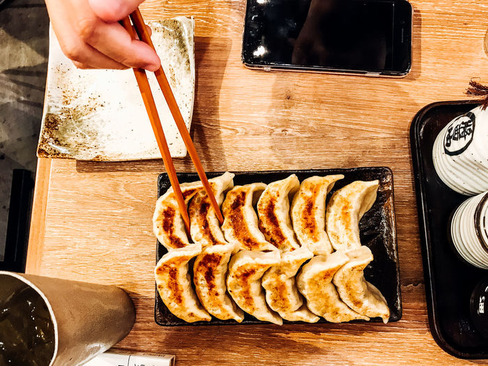 Dinner Eating EyeEm Selects EyeEmNewHere Lunch ShareTheMeal Chopsticks Close-up Day Food Food And Drink Freshness Gyoza Healthy Eating Human Body Part Human Hand Indoors  Mealtime Men One Man Only One Person People Preparation  Ready-to-eat Real People Table Wood - Material