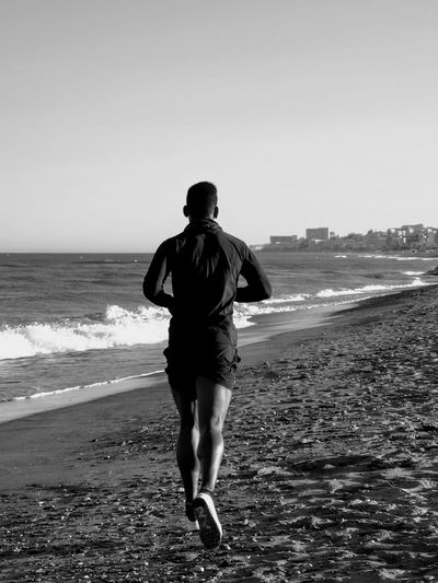 Rear view of man running at beach against clear sky