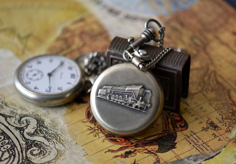 Close-up of pocket watches on map