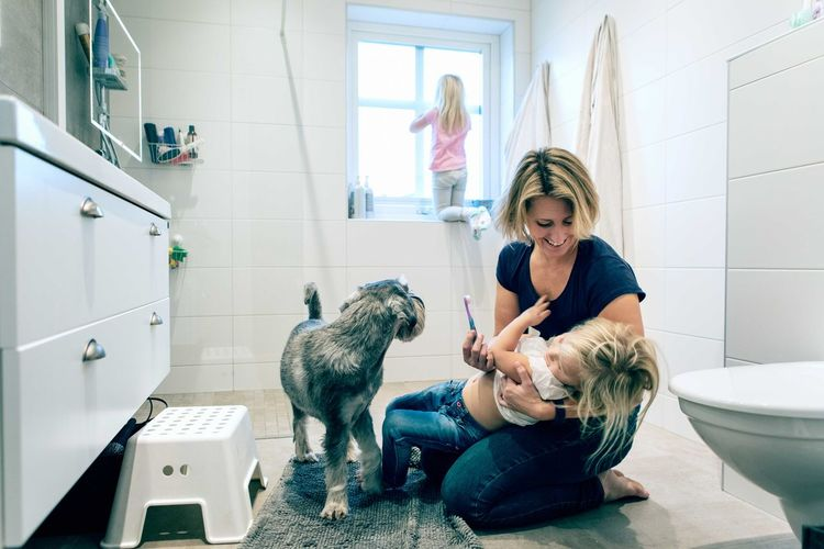 Woman with dog in bathroom