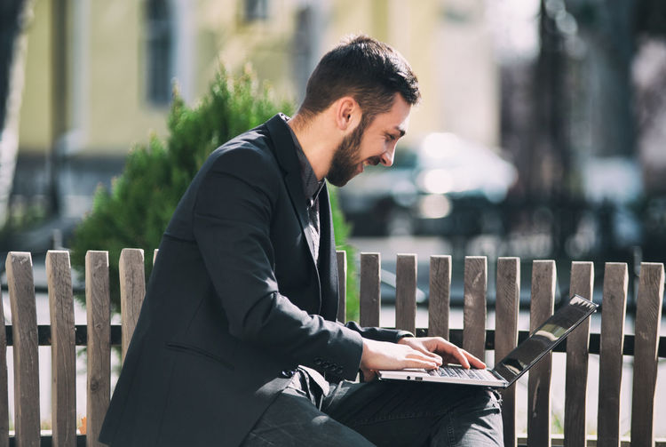 One Person Three Quarter Length Focus On Foreground Real People Young Men Sitting Young Adult Day Men Railing Seat Lifestyles Side View Connection Business Person Looking Males  Well-dressed Outdoors