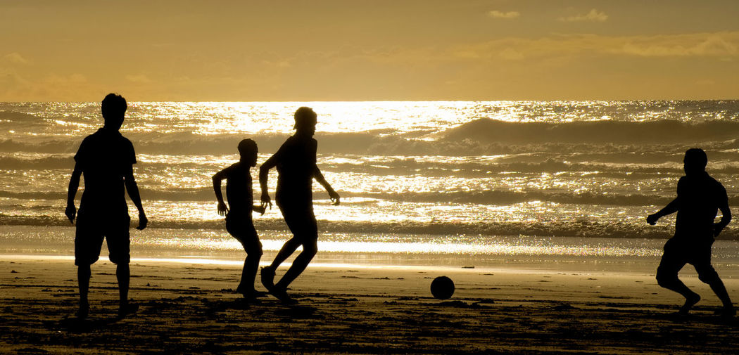Silhouette men playing soccer at beach against sky during sunset