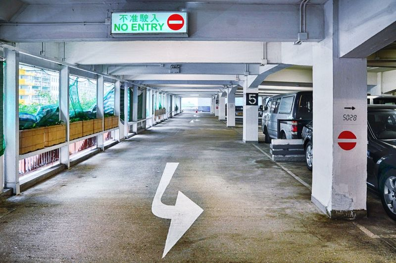 View of arrow sign on parking lot floor