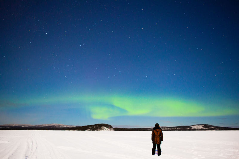 Rear view of man standing on snow covered land against sky at night