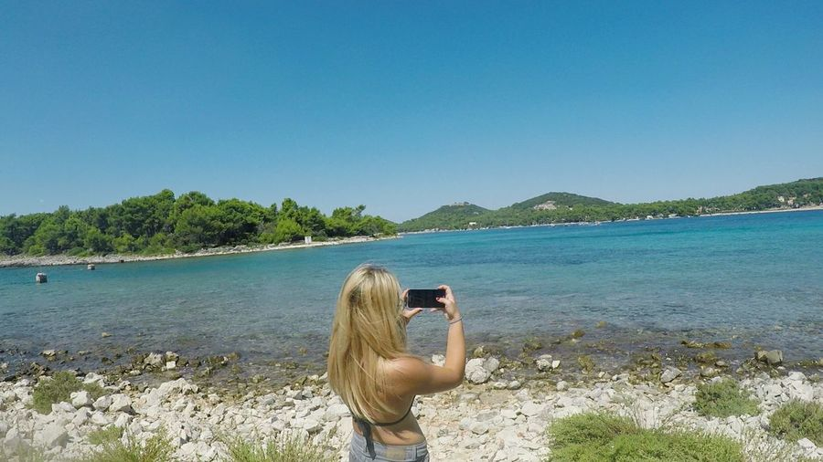 Rear view of woman photographing sea with smart phone against clear sky