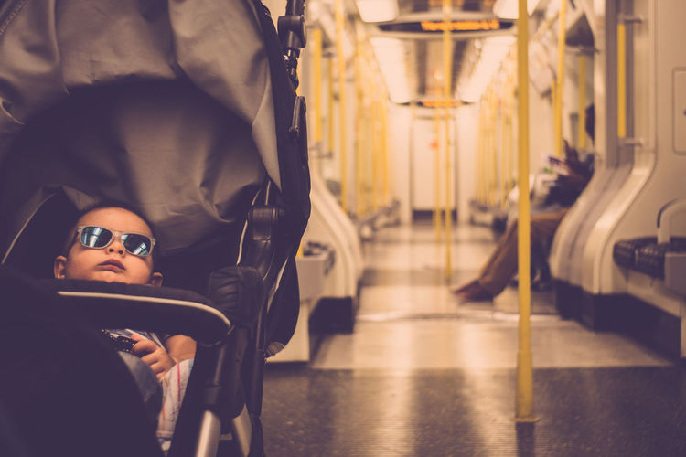 Cute boy relaxing on baby carriage in train