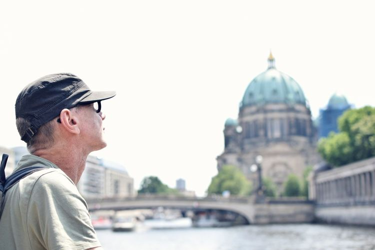 Mature man by river with berlin cathedral in background