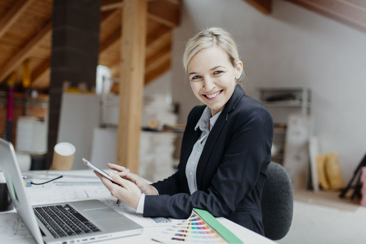 Business Businesswoman Cheerful Connection Corporate Business Happiness Indoors  Laptop Looking At Camera Office One Person One Woman Only One Young Woman Only Portrait Real People Smiling Suit Technology Using Laptop Well-dressed Wireless Technology Women Working Young Adult Young Women