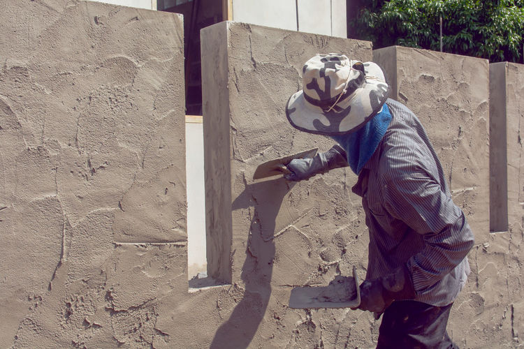 Construction workers plastering building wall using cement plaster. Plastering Plasterer Plaster Wall Worker Renovation Construction Man Builder Renovating Building Indoors  Professional Repair Manual Male House Contractor Work Working Putty Plasterwork Tool Occupation Uniform Painter Concrete Cement Home Blue Trowel person Interior Stucco Spatula Surface Room Industry Industrial Real Estate Improvement Craftsman Workman WorkWear Coating Overall Repairer Concept Sanding