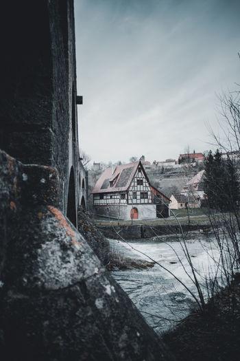 River by buildings in town against sky
