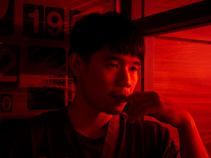 Thoughtful young man looking away in red illuminated home