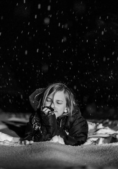 Portrait of kid lying on snow at night