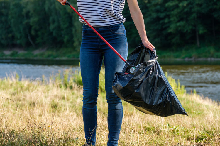 Midsection of woman collecting garbage on land against river