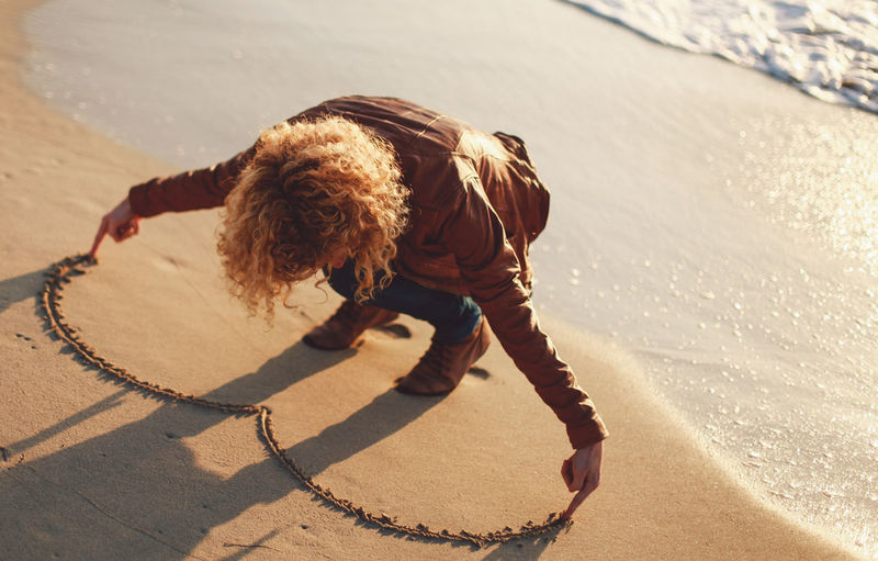 High angle view of woman making heart shape on sand at beach
