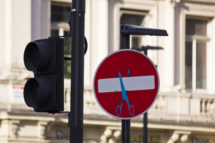 Stop road sign with scissors drawn on it, street art in the center of london
