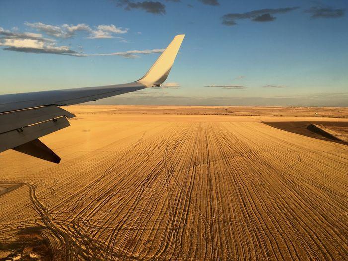 Airplane Flying Over Sand Dune In Desert Against Sky