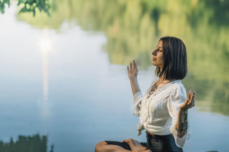 Yoga meditation retreat. woman sitting in lotus position with fingers in chin mudra and meditating