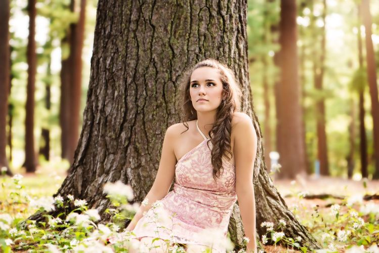 Portrait of young woman in tree trunk in forest