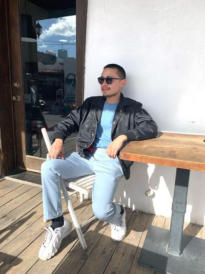 Young man wearing sunglasses while sitting on chair against wall