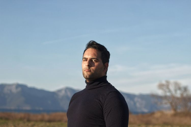 Portrait of man standing on landscape against sky