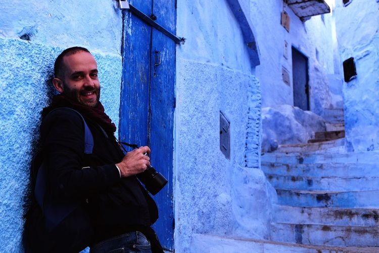 Portrait of happy man leaning on wall while holding digital camera