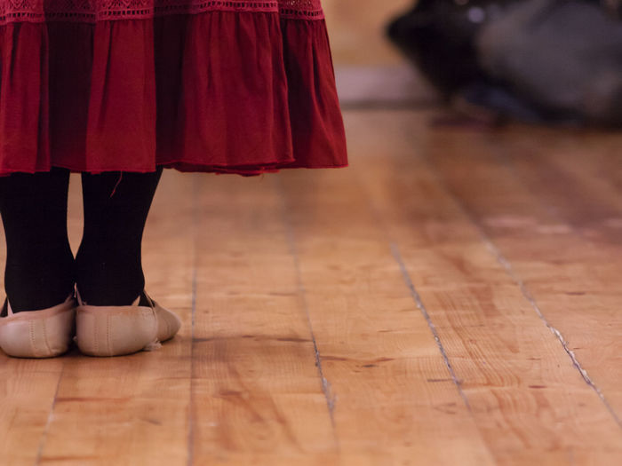 Rear view of a girl, standing on a wooden floor, during rehearsal