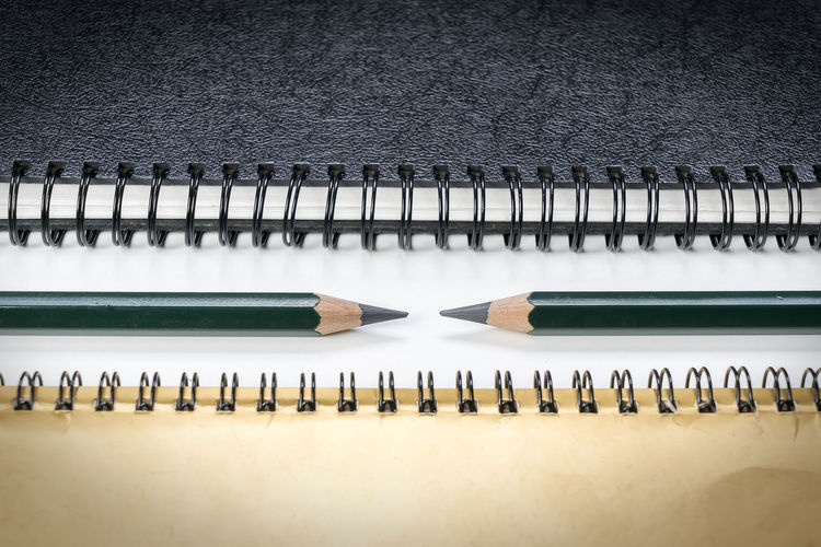 High angle view of pencils and spiral notebooks on table