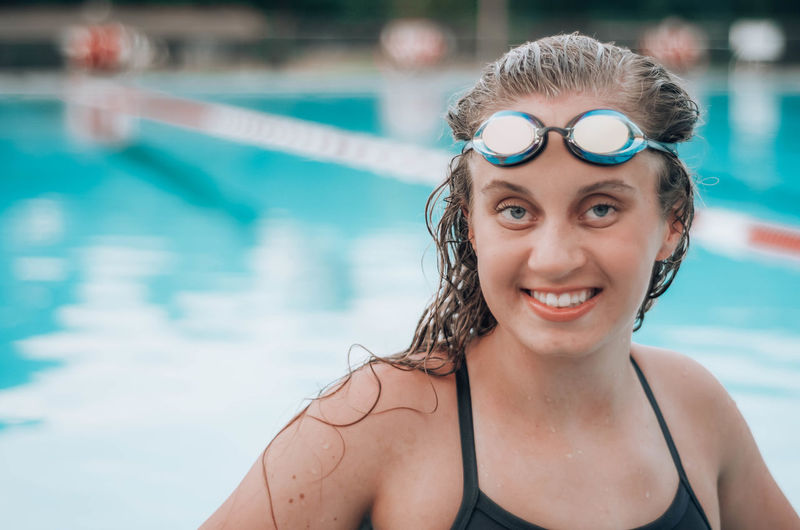 Portrait of smiling young woman in swimming in pool