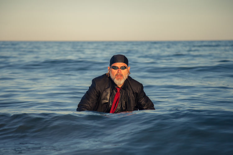 Well-dressed mature man swimming in sea against clear sky during sunset