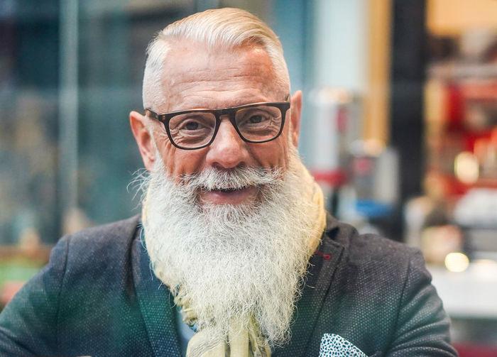 Portrait of bearded man wearing eyeglasses sitting in cafe