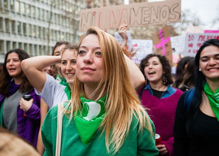 Portrait of smiling women standing against people