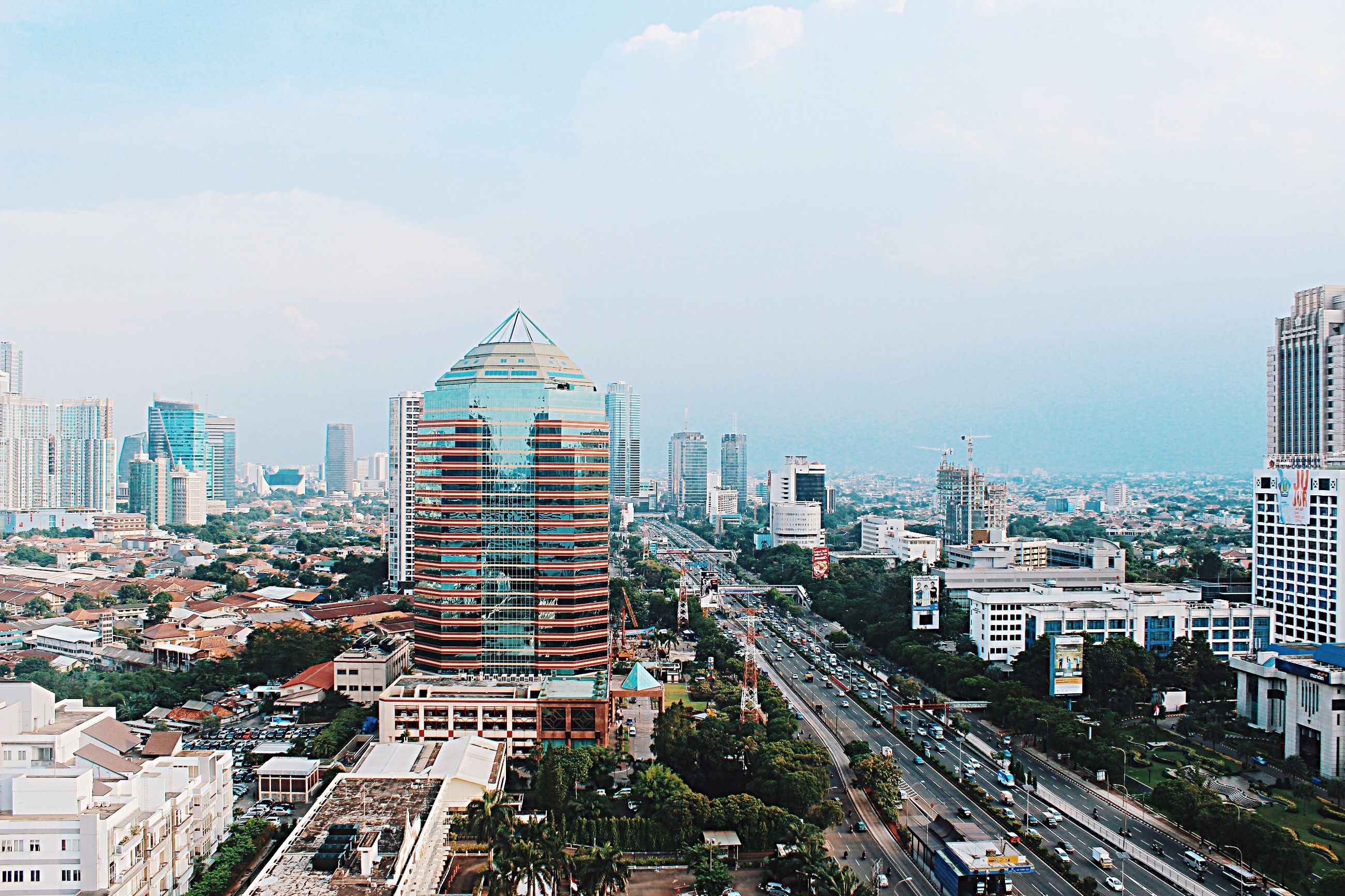 building exterior, architecture, city, built structure, cityscape, transportation, road, high angle view, street, car, sky, residential district, residential building, city life, land vehicle, residential structure, city street, building, the way forward, outdoors