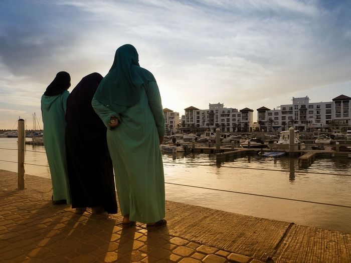 Rear view of women wearing burka while standing by river against sky