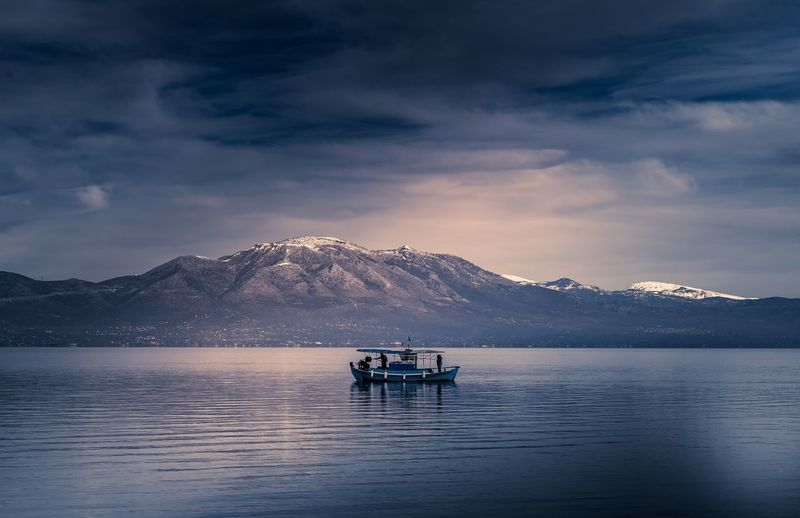 Boat in lake against mountains and sky