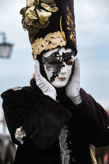 Carnival Carnival In Venice Venice, Italy Carnival Carnival Masks Celebration Costume Day Disguise Focus On Foreground Headdress Headwear Leisure Activity Lifestyles Mask - Disguise One Person Outdoors People Real People Sky Venetian Event Venetian Mask Venetian Masks Waist Up Wearing