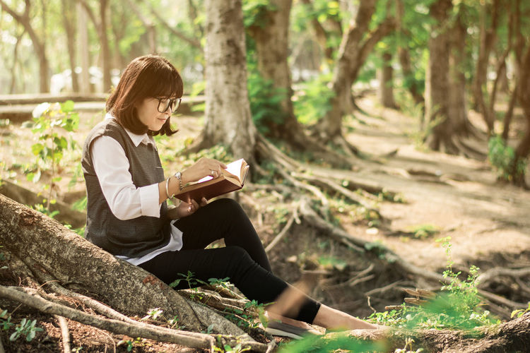 Woman Reading Book While Sitting In Forest