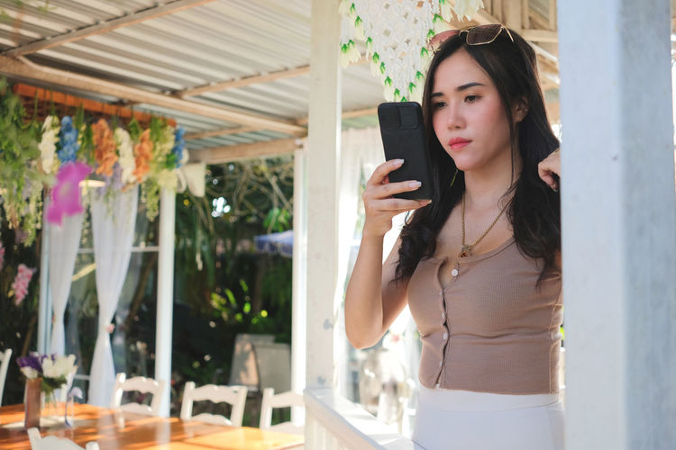 Young woman holding smart phone while sanding outdoors