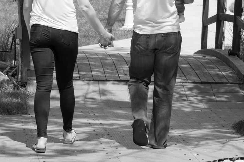 Couple Walking Together Holding Hands in Black & White Black & White Couple Family Holding Hands Married Relationship Black And White Casual Clothing Human Leg Leisure Activity Lifestyles Low Section Marriage  Outdoors People Real People Togetherness Two People Walking