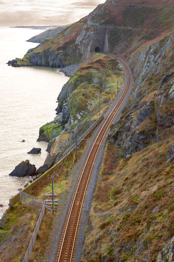 High angle view of railroad track by sea and mountain