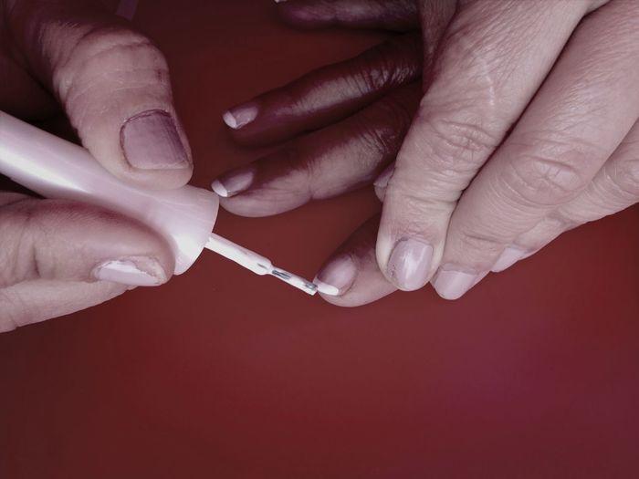 Close-up of hands applying nail varnish